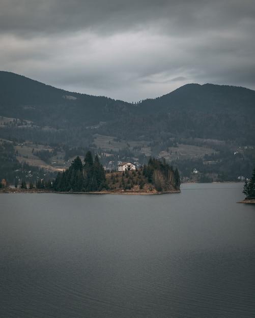 Вертикальный снимок дома на берегу моря в окружении деревьев и гор Бесплатные Фотографии