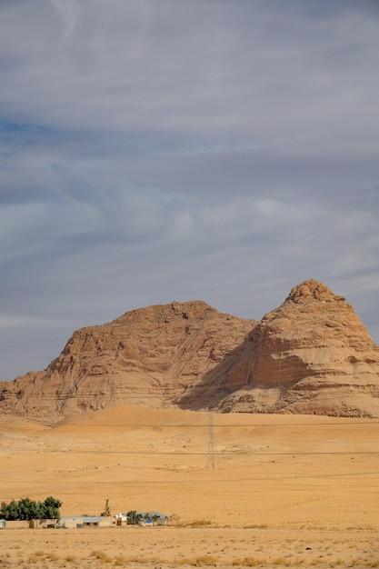 曇り空の下で砂漠の大きな崖の垂直ショット 無料写真