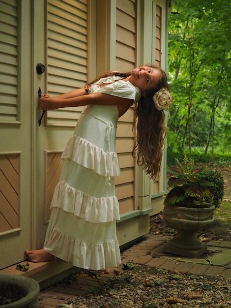Вертикальный снимок маленькой девочки с длинными волосами в белом платье, закрывающей дверь дома Бесплатные Фотографии