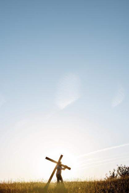 青い空と芝生のフィールドで大きな木製の十字架を運ぶ男性の垂直ショット 無料写真