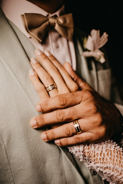 Вертикальный снимок мужчины, держащего женщину за руку на груди Бесплатные Фотографии