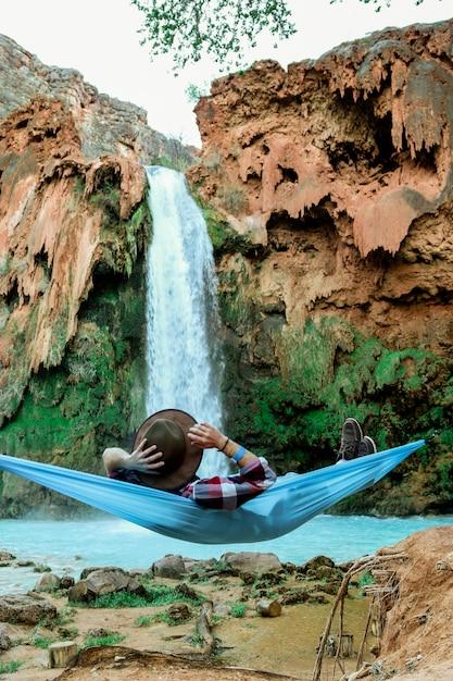 丘から流れ落ちる滝の横にあるハンモックに横になっている男性の垂直ショット 無料写真