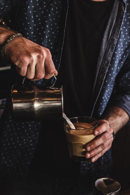 Вертикальный выброс мужчины наливая молоко в стакан кофе Бесплатные Фотографии