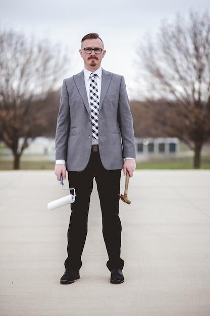 Вертикальный снимок мужчины в костюме, держащего молоток и кисть на улице Бесплатные Фотографии