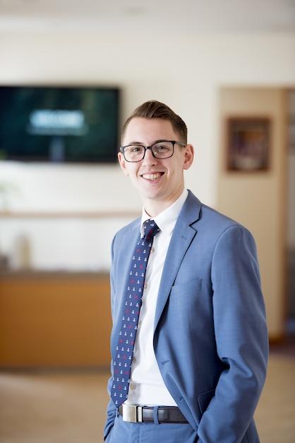 Вертикальный снимок мужчины в костюме и галстуке, стоящего в классе Бесплатные Фотографии