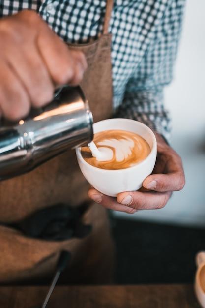 カフェでカプチーノカップに牛乳を注ぐ男の垂直ショット 無料写真