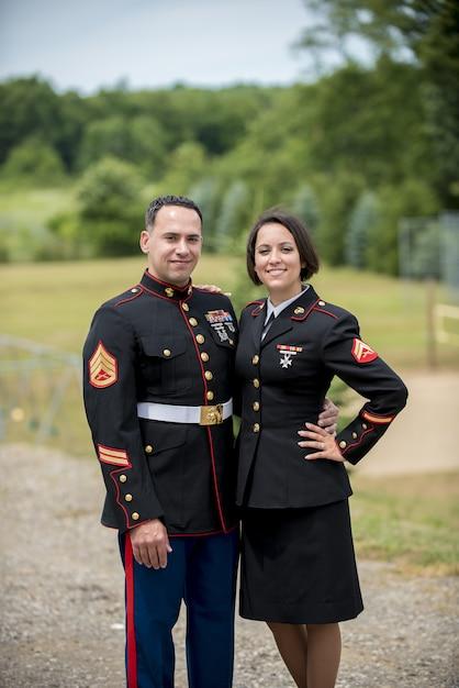 Вертикальный снимок военной пары, обниматься, улыбаясь в камеру Бесплатные Фотографии