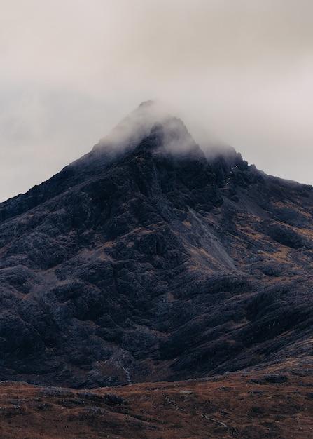 Вертикальный снимок горы, покрытой облаком тумана в шотландии, остров скай Бесплатные Фотографии
