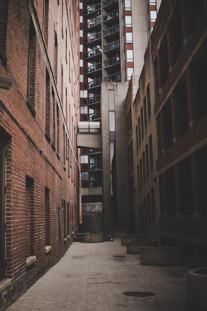 Вертикальный снимок узкого переулка между кирпичными домами и многоэтажным домом Бесплатные Фотографии