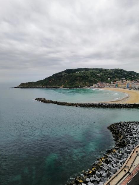 スペイン、サンセバスチャンのリゾートタウンにある熱帯のビーチの完璧な風景の垂直ショット 無料写真