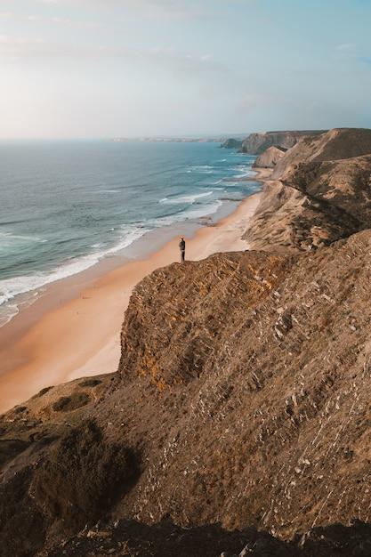 Вертикальный выброс человека на скале, глядя на красивый океан в алгарве, португалия Бесплатные Фотографии