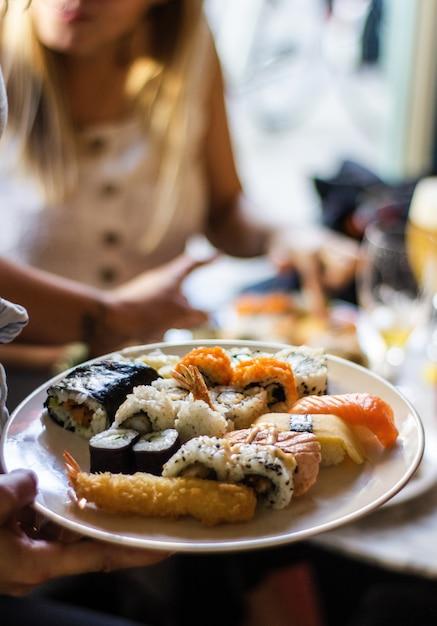 Вертикальный снимок руки человека, держащего тарелку суши Бесплатные Фотографии