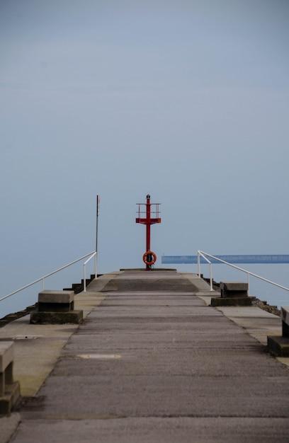 Вертикальный снимок пирса, ведущего к океану под чистым небом Бесплатные Фотографии