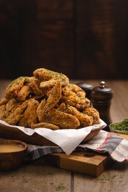 나무 테이블에 튀긴 닭 날개와 일부 향신료의 더미의 세로 샷 무료 사진