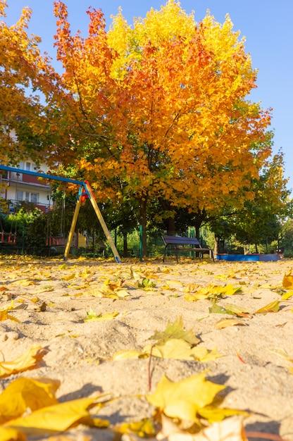 Вертикальный снимок детской площадки в парке с разноцветными листьями в земле осенью Бесплатные Фотографии