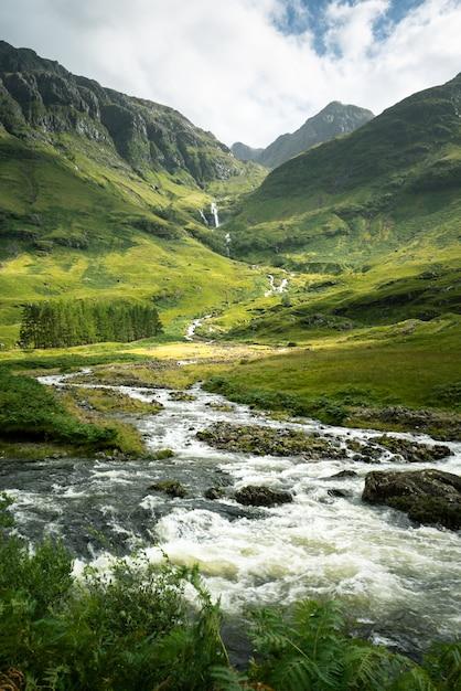スコットランドの山々と牧草地に囲まれた川の垂直ショット 無料写真
