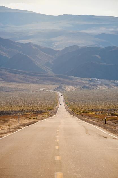 カリフォルニアでキャプチャされた壮大な山々を通る道路の垂直ショット 無料写真