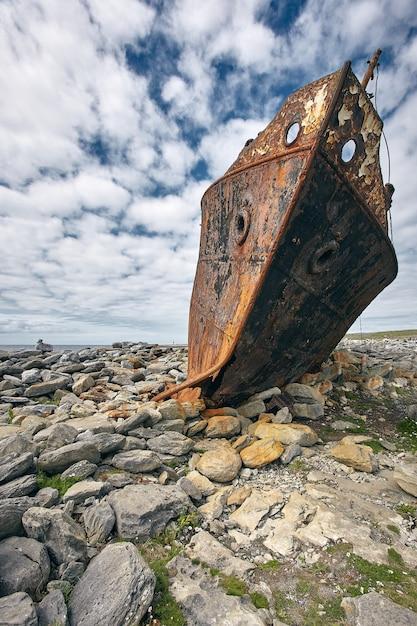 Вертикальный снимок ржавого корпуса корабля plassy на островах аран, ирландия Бесплатные Фотографии