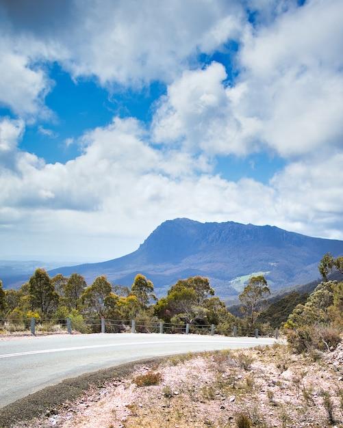 山を背景に地平線上で色あせた風光明媚な道路の垂直ショット 無料写真
