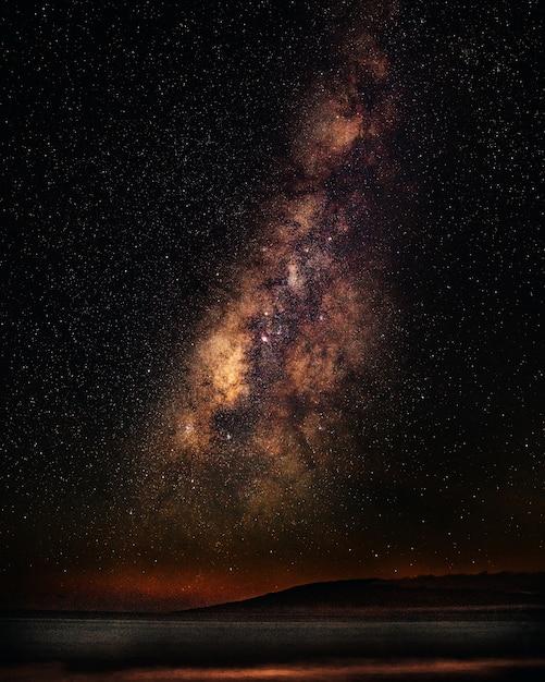 은하수와 별이 빛나는 하늘 아래 바다의 세로 샷 무료 사진