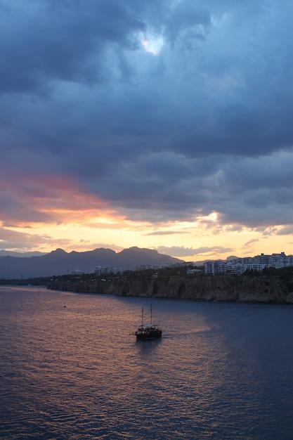 日没時に暗い雲の下の海で1つのボートの垂直ショット 無料写真