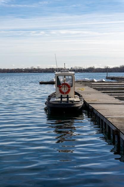 Вертикальный снимок небольшой пришвартованной лодки в дневное время Бесплатные Фотографии
