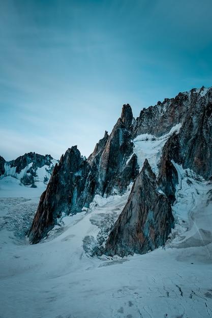 青空の下で山の近くの雪に覆われた丘の垂直ショット 無料写真