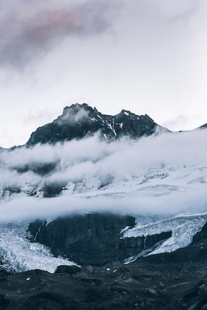 澄んだ空と雲の上の雪に覆われた山の頂上の垂直方向のショット 無料写真