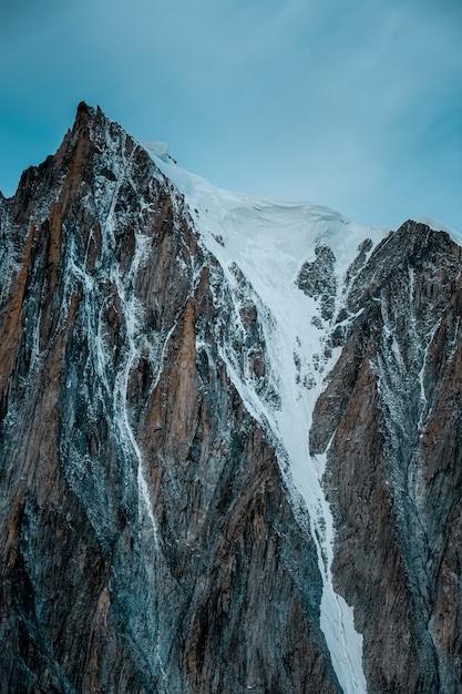 澄んだ空を背景に雪山の垂直ショット 無料写真