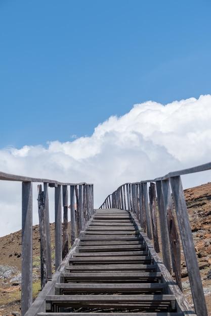エクアドルのガラパゴス諸島の空に触れる山々に通じる階段の垂直ショット 無料写真
