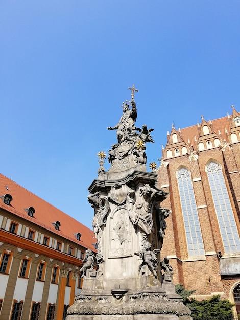 Вертикальный снимок статуи возле собора святого иоанна крестителя варшава, польша Бесплатные Фотографии
