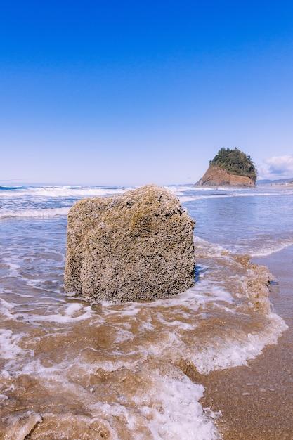 Вертикальный снимок камня в океане под голубым ясным небом Бесплатные Фотографии