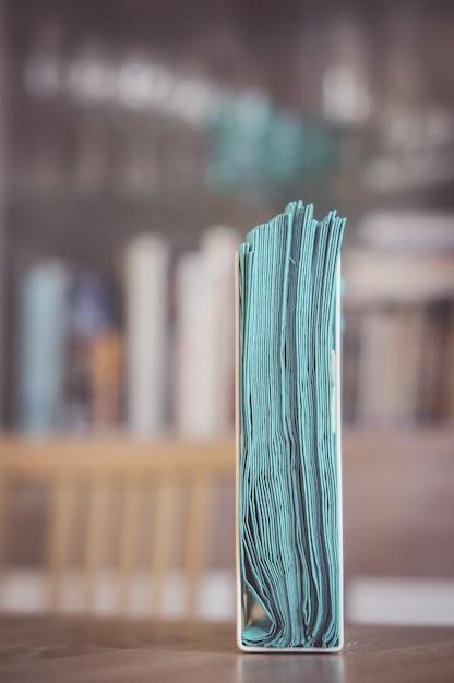 Вертикальный снимок держателя салфеток на деревянной поверхности Бесплатные Фотографии