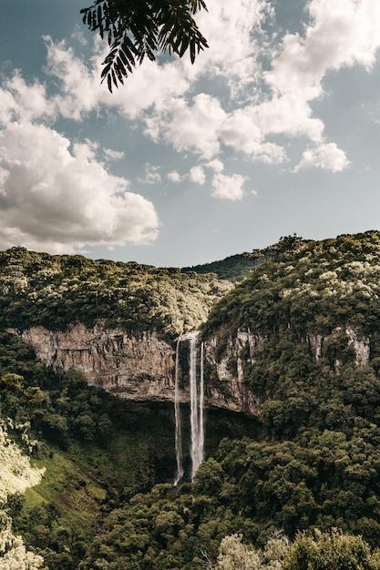 Вертикальная съемка водопада течет с высокой скалы, покрытой зелеными деревьями Бесплатные Фотографии
