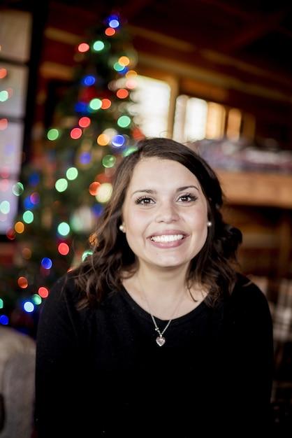Вертикальный снимок белой женщины, улыбаясь перед праздничным веселым Бесплатные Фотографии