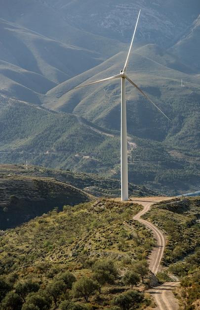 山の後ろの緑のフィールドに立っている白い風ファンの垂直ショット 無料写真