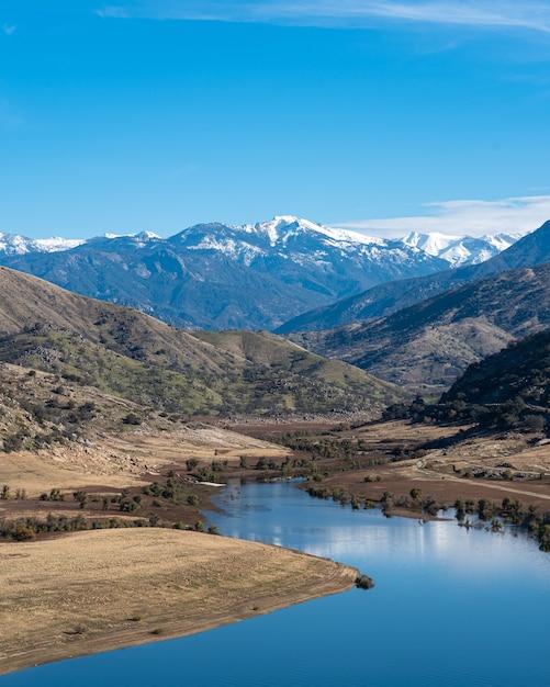 Вертикальный снимок извилистой реки с величественными горами и голубым небом Бесплатные Фотографии