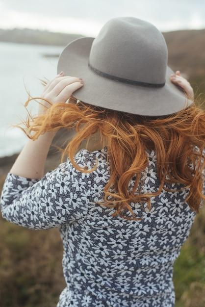 遠くに海と木々と帽子をかぶっている女性の垂直ショット 無料写真