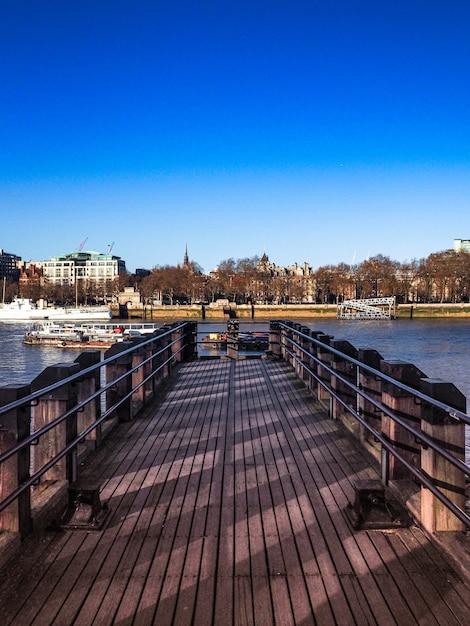 도시와 강으로 이어지는 나무 독의 수직 샷 무료 사진