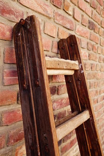나무 접이식 사다리의 세로 샷은 벽돌 벽에 기대어 무료 사진