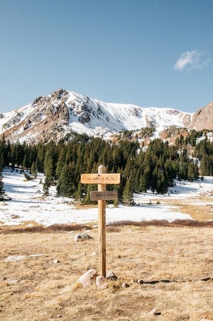 Вертикальная съемка деревянного знака с деревьями и снежными горами на заднем плане под ясным небом Бесплатные Фотографии