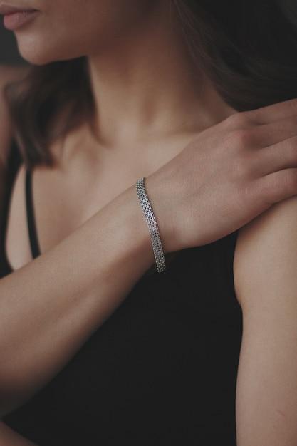 아름다운 실버 팔찌를 착용하는 젊은 여성의 세로 샷 무료 사진