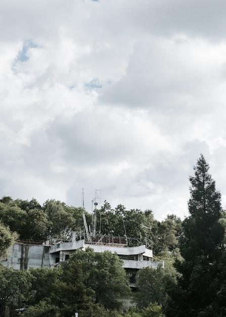 Вертикальный снимок заброшенного здания посреди леса под облачным небом Бесплатные Фотографии