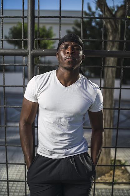 Вертикальный снимок афроамериканца в белой рубашке, опирающегося на забор Бесплатные Фотографии