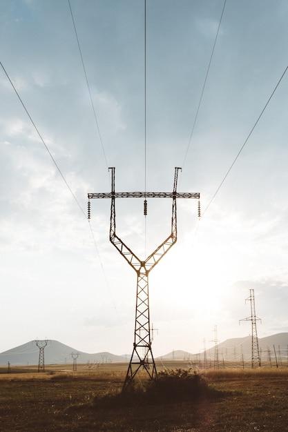 Вертикальный снимок электрического столба с металлическими перилами наверху под пасмурным небом Бесплатные Фотографии