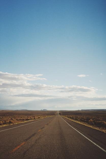 Вертикальная съемка пустой дороги посреди пустыни под красивым голубым небом Бесплатные Фотографии