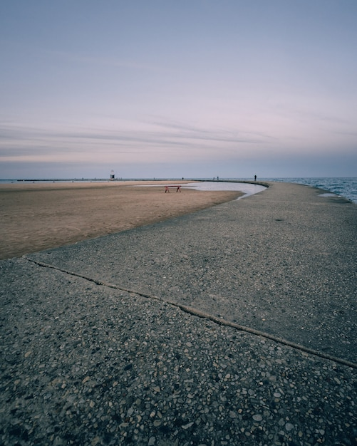 Вертикальный снимок пустого берега моря и ясного голубого неба Бесплатные Фотографии