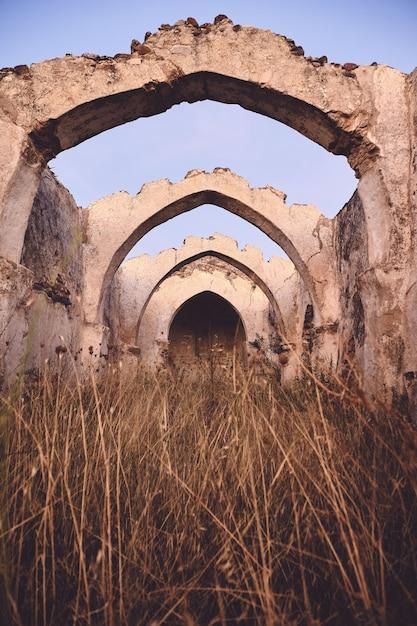 Вертикальный снимок старых древних руин со сводчатым потолком в сухом травянистом поле под голубым небом Бесплатные Фотографии
