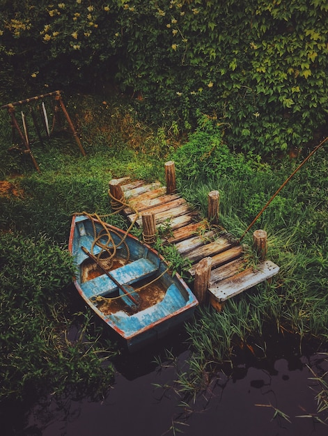 緑に囲まれた木製のドックの近くの水で古いボートの垂直ショット 無料写真