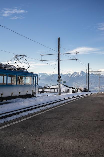 Вертикальный снимок воздушной линии возле железной дороги электропоезда под ясным голубым небом Бесплатные Фотографии